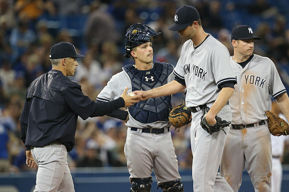 TORONTO, CANADA - MAY 4: Chris Martin #57 of the New York Yankees exits the game as he is relieved by manager Joe Girardi #28 as John Ryan Murphy #66 looks on in the eighth inning during MLB game action against the Toronto Blue Jays on May 4, 2015 at Rogers Centre in Toronto, Ontario, Canada. (Photo by Tom Szczerbowski/Getty Images)