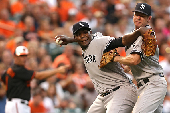 BALTIMORE, MD - JUNE 12: Starting pitcher Michael Pineda #35 of the New York Yankees collides with teammate third baseman Chase Headley #12 as he tries to throw out Jimmy Paredes #38 of the Baltimore Orioles in the third inning at Oriole Park at Camden Yards on June 12, 2015 in Baltimore, Maryland. (Photo by Patrick Smith/Getty Images)