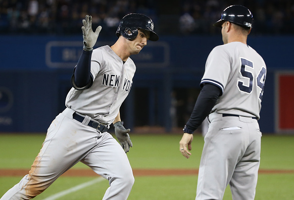 TORONTO, CANADA - SEPTEMBER 22: Greg Bird #31 of the New York Yankees is congratulated by third base coach Joe Espada #54 after hitting a three-run home run in the 10th inning during MLB game action against the Toronto Blue Jays on September 22, 2015 at Rogers Centre in Toronto, Ontario, Canada. (Photo by Tom Szczerbowski/Getty Images)