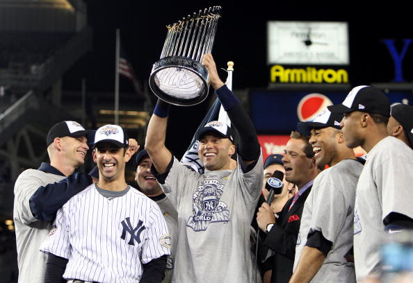 NEW YORK - NOVEMBER 04:  Derek Jeter #2 of the New York Yankees holds up the trophy as he celebrates with A.J. Burnett (L), Jorge Posada (2nd L), Mariano Rivera (2nd R) and Robinson Cano after their 7-3 win against the Philadelphia Phillies in Game Six of the 2009 MLB World Series at Yankee Stadium on November 4, 2009 in the Bronx borough of New York City.  (Photo by Jed Jacobsohn/Getty Images)