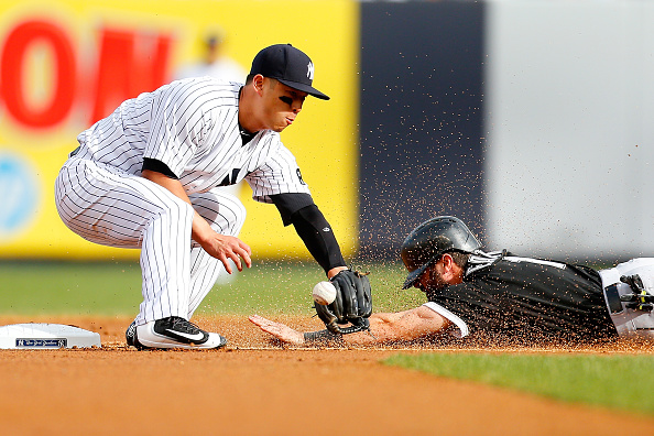 NEW YORK, NY - SEPTEMBER 26:  Robert Refsnyder #64 of the New York Yankees is unable to handle the throw as Adam Eaton #1 of the Chicago White Sox steals second base in the first inning at Yankee Stadium on September 26, 2015 in the Bronx borough of New York City.  (Photo by Mike Stobe/Getty Images)