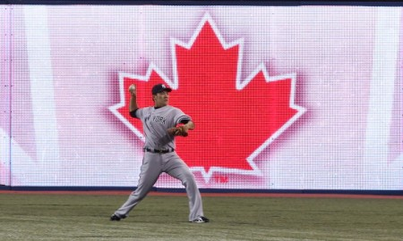 TORONTO, CANADA - APRIL 4: Masahiro Tanaka #19 of the New York Yankees warms up doing long toss in the outfield before the start of MLB game action against the Toronto Blue Jays on April 4, 2014 at Rogers Centre in Toronto, Ontario, Canada. (Photo by Tom Szczerbowski/Getty Images)