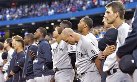 New York Yankees players, coaches and staff take part in a moment of silence as they wear the No. 8 to remember Hall of Fame catcher Yogi Berra, who died Tuesday, before the Yankees' baseball game against the Toronto Blue Jays in Toronto on Wednesday, Sept. 23, 2015. (Nathan Denette/The Canadian Press via AP)